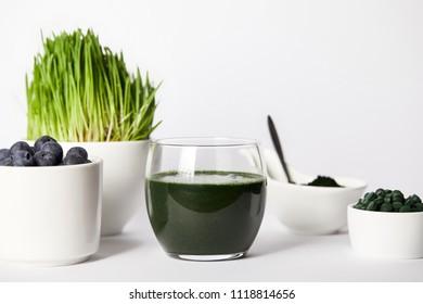 spirulina smoothie, spoon, cups with spirulina grass and blueberries, bowls with spirulina powder and spirulina pills on grey background