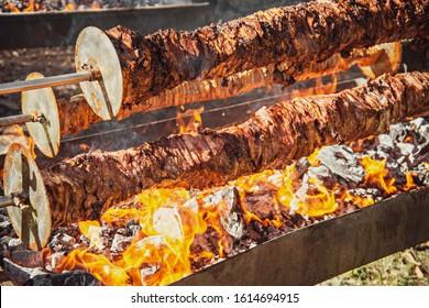 Spit roast meat on hardwood charcoal BBQ rotisserie