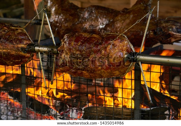 Spit roasting meat over fire