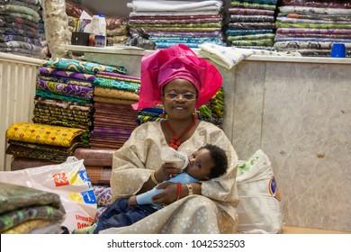 Spitalfields, London, England - August 6 2011 : African woman in traditional dress and headwear bottle feeding a baby in a fabric shop in Petticoat Lane, London