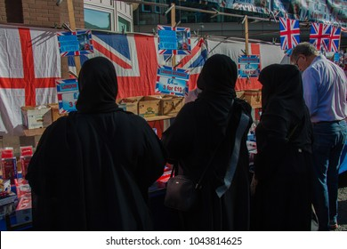 Spitalfields, London, UK - September 28 2014 : Group of three Muslim women wearing niqabs in front of a stall with British flags in Petticoat Lane Sunday Market in London