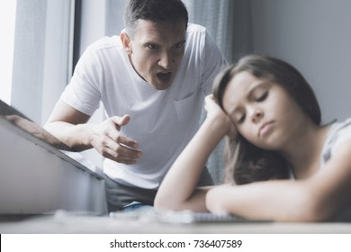 The spiteful father screams at his daughter, who sits at the table, propping her head in her hands and closing her eyes
