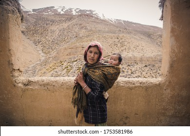 SPITI, HIMACHAL PRADESH, INDIA - CIRCA JUNE 2015: Indian Woman Carrying Baby on her back in Spiti Valley. The traditional way of carrying a child in a sling in rural & remote Indian Mountains. Mother.