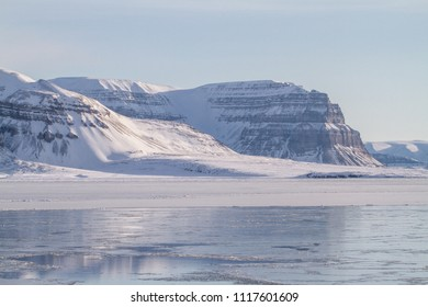 Spitsbergen - Svalbard and Jan Mayen islands ailing in the frozen arctic blue sea with mountains in the background