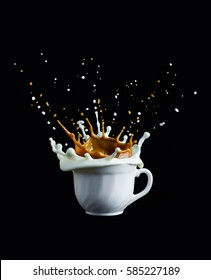 Splash of coffee and milk in white cup isolated on black background movement action