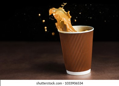 Splash of coffee in a paper takeaway cup on black background