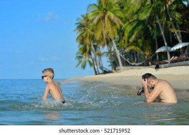 A lot of splash: father and son splatter each other with cool saltwater, theyâ??re fighting and having fun. 7 years old cute blond boy wins