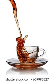 Splash in glass cup of black tea isolated on white background