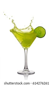 Splash in glass of green alcoholic cocktail drink with lime isolated on white background