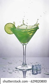 Splash in glass of green mint alcoholic cocktail drink with lime and ice cube on gray gradient background