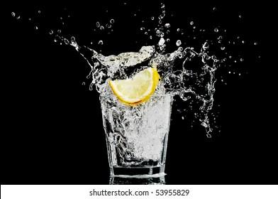 Splash in einem Glas mit Zitrone und Eis auf schwarzem Hintergrund