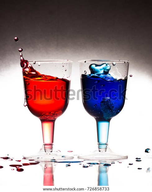 Splash of ice cubes into red and blue drinks depicting 'his and hers' celebratory drinks