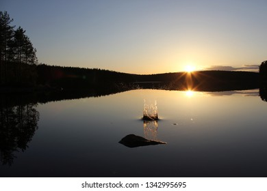 A splash on the surface of a still lake in sunset in Sweden.