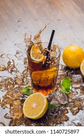 Splash. Refreshingly cold ice tea with lemon and mint on wooden table
