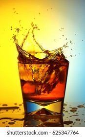 A splash from thrown ice in a glass of whiskey