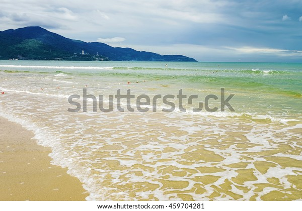 Splash of water at the China Beach in Danang in Vietnam. It is also called Non Nuoc Beach. South China Sea and Marble Mountains on the background.
