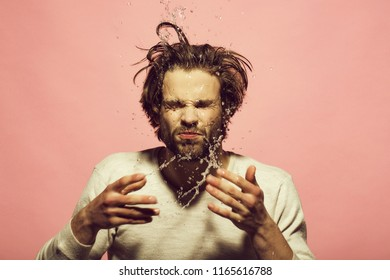 splash of water drops of man washing face in morning. guy with long hair refreshing in underwear on pink background, hygiene and skincare, health and wakeup, everyday life, barbershop