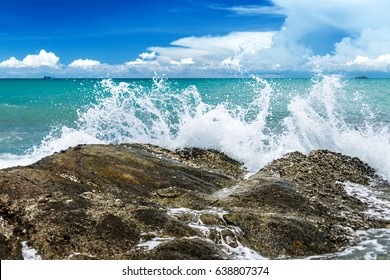 Splash water of sea wave attack to the rock phot  with outdoor sunny  lighting .