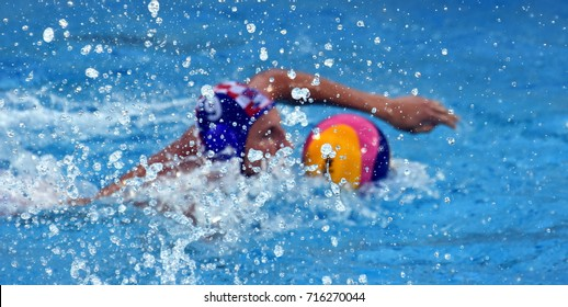 Splash of water, waterdrops are in focus. Waterpolo player swimming with a ball in the background.