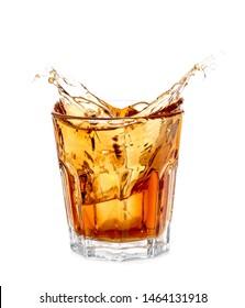 Splash of whiskey in glass on white background