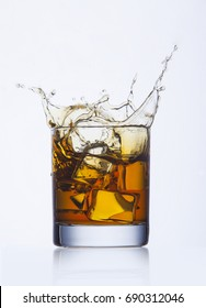 Splash of whiskey in glass on white background