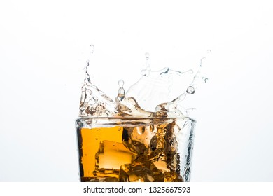 Splash of whiskey from ice cubes on a white background. Concept of alcoholic drinks with ice, whiskey or brandy, apple juice and cooling drinks.