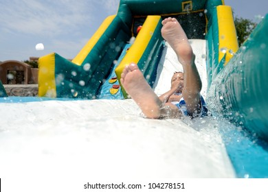 Splash! Young boy sliding down an inflatable water slide feet first while splashing water.