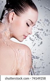 Splashes and drops of water around the female face with clean skin - vertical