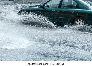 splashes of rain water from car wheels during heavy rain