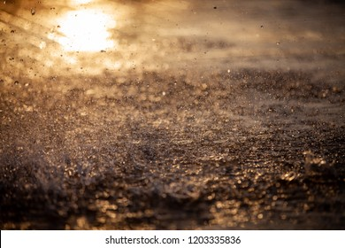 Splashes of water and bokeh of Water on a Sunset Background.