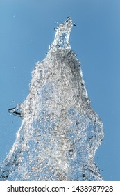 Splashes of water. Fountain, a jet of water against the blue sky.