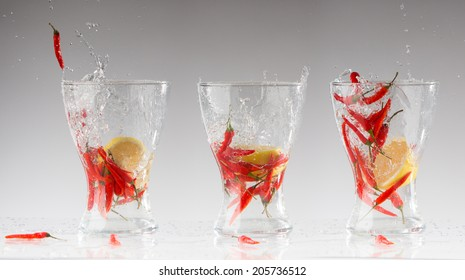 splashes of water from the red hot pepper and lemon in a glass