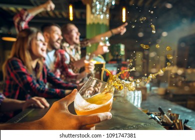 Splashing beer in the foreground and in focus. Sport, people, leisure, friendship and entertainment concept - happy football fans or male friends drinking beer and celebrating victory at bar or pub