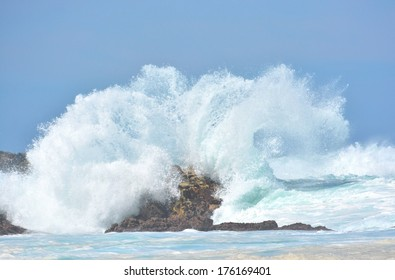 A splashing big wave crashing into the rocks in the rough wild water of the Indian Ocean on a stormy sunny day during springtime in South Africa.