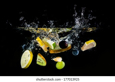 Splashing fresh fruit on water on black background