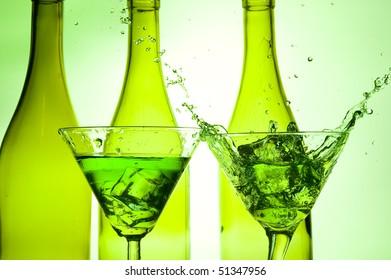 Splashing green cocktail in martiniglass