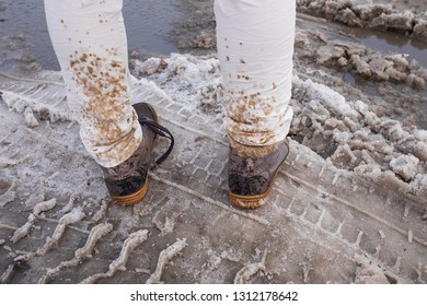 Splashing and melting snow drops on white jeans. Woman walking outdoor in spring.