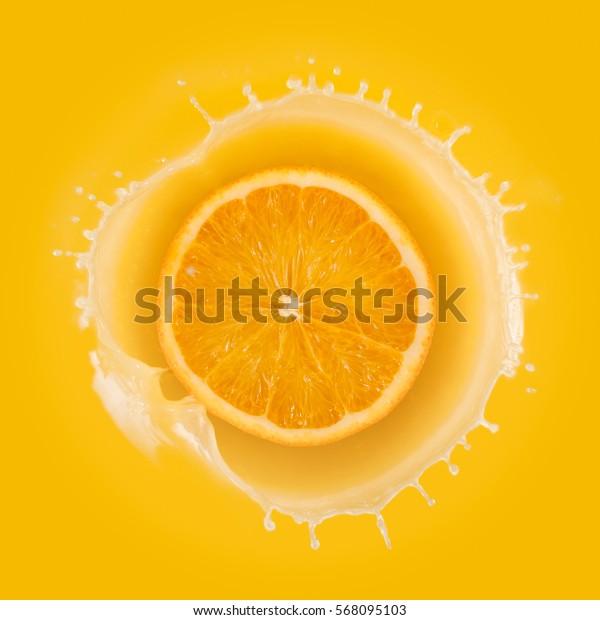 splashing orange juice with orange against yellow background.