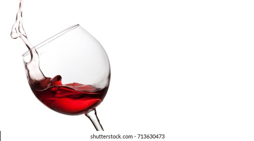Splashing red wine in crystal wineglass. white background. copy space