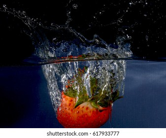 Splashing strawberry on water on black background with bubbles.