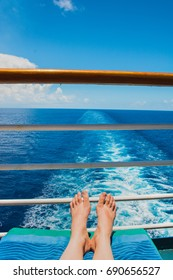 Splashing trail in ocean after cruise ship with feet on boat