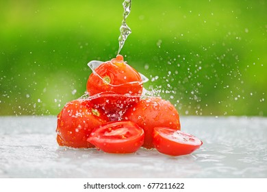 Splashing water and tomato on green natural background. Summer.
