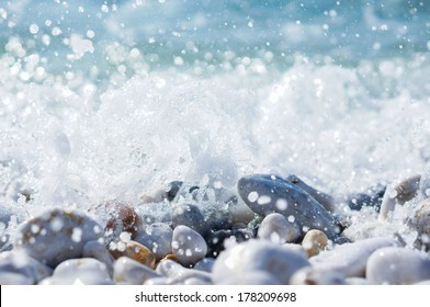 splashing waves over pebbles