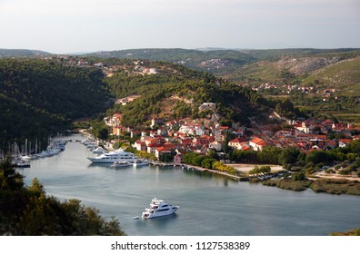 Splendid aerial view on small town Skradin on Krka river, Dalmatia, Croatia. Popular tourist destination for summer vacation. Medieval fortress of Turina on a hill over the town. Many yachts in a bay.