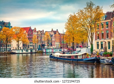 Splendid autumn scene of Amsterdam city. Famous Dutch channels and great cityscape. Colorful morning landscape in Netherlands, Europe. Traveling concept background.