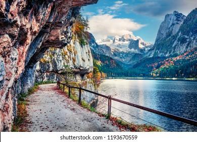 Splendid autumn scene of Vorderer ( Gosausee ) lake with Dachstein glacieron background. Picturesque morning view of Austrian Alps, Upper Austria, Europe. Traveling concept background.