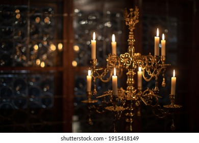 Splendid chandelier with lit candles in a beautiful room of an old mansion