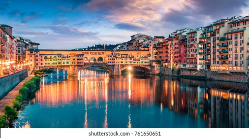 Splendid medieval arched river bridge with Roman origins - Ponte Vecchio over Arno river. Colorful spring sunset view of Florence, Italy, Europe. Traveling concept background.