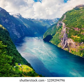 Splendid summer scene of Sunnylvsfjorden fjord, Geiranger village location, western Norway. Beautiful morning view of famous Seven Sisters waterfalls. Beauty of nature concept background.