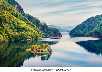 Splendid summer view of small island with red painted Norwegian building on Lovrafjorden flord, North sea. Colorful morning view in Norway. Beauty of nature concept background.